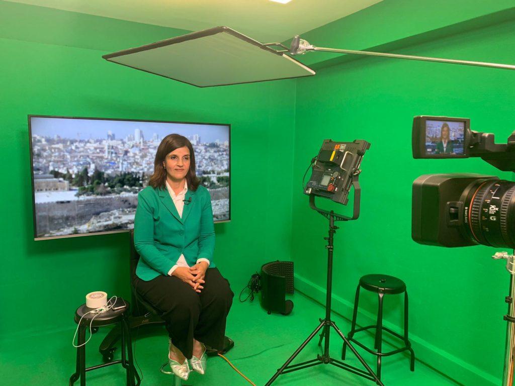 אולפן ירוק עם ציוד צילום ואישה יושבת על כיסא לבושה בג'קט ירוק עם מסך מאחוריה ועליו תמונה של עיר