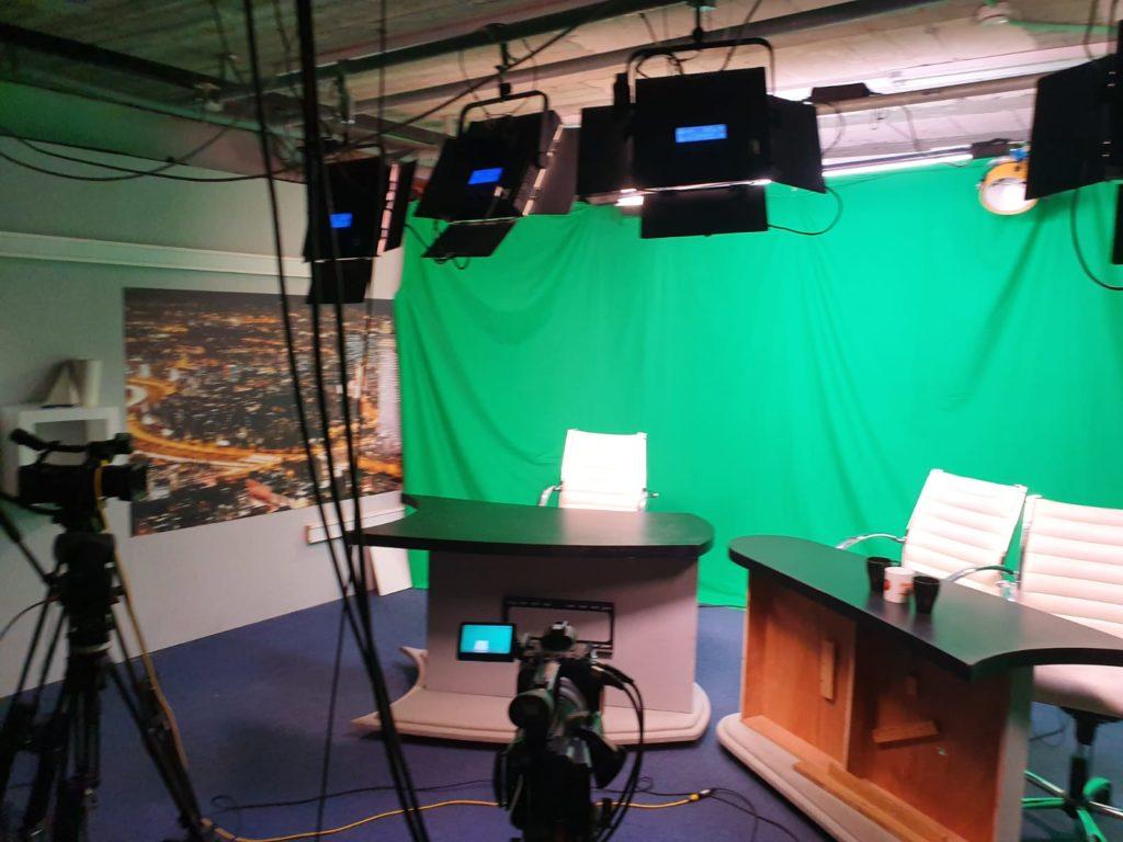 צילום מתוך אולפנים שצילמנו בהם ציוד צילום ופרוז'קטורים המכוונים ישר על מסך ירוק ולפניו שולחנות ולידם כיסאות לבנים