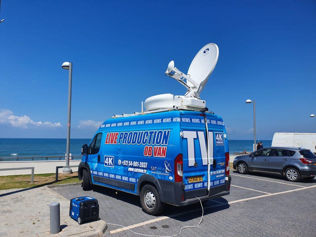 ניידת כחולה המשמשת למטרת שידור חי לפייסבוק וצילום עם לווין לבן על הגג בחניה ליד החוף